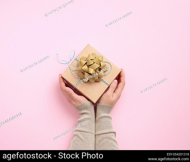 female hand holds a square box with a golden bow on a pink background, concept of a congratulation on a happy birthday, place for text