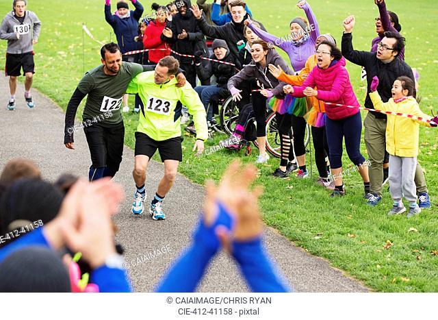 Man helping injured runner finish charity run in park