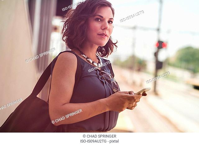 Mid adult woman waiting at train station, holding smartphone