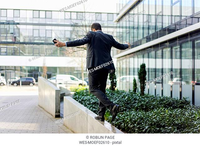 Rear view of businessman balancing on a wall outside office building