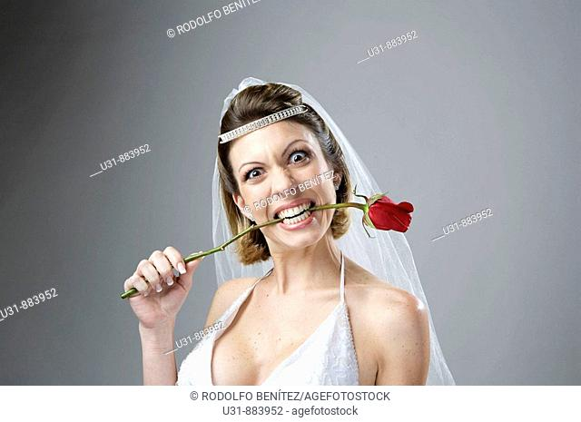 Bride in her 20s bites a red rose