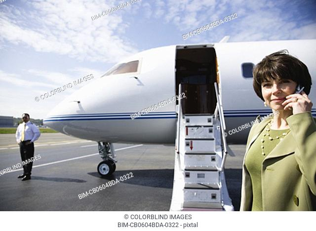 Businesswoman using cell phone on tarmac in front of private airplane