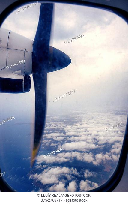 View of airplane engine and propeller through window, with clouds and sea in background