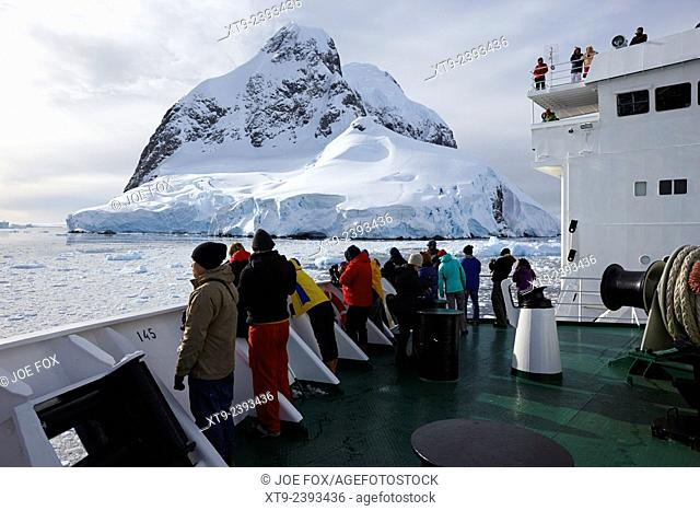 passengers on board ship passing roullin point at the southern end of booth island and the lemaire channel antarctica
