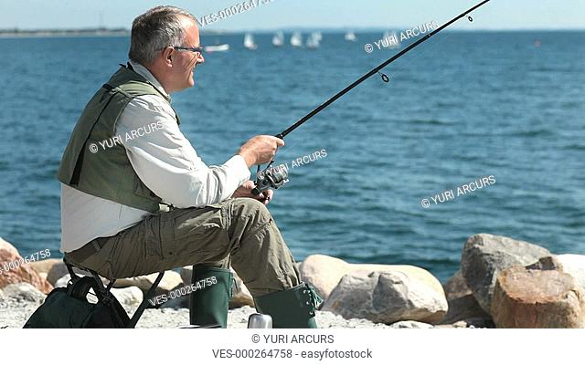 Happy retired man fishing on some rocks with boats on the water in the background, turning to smile at the camera