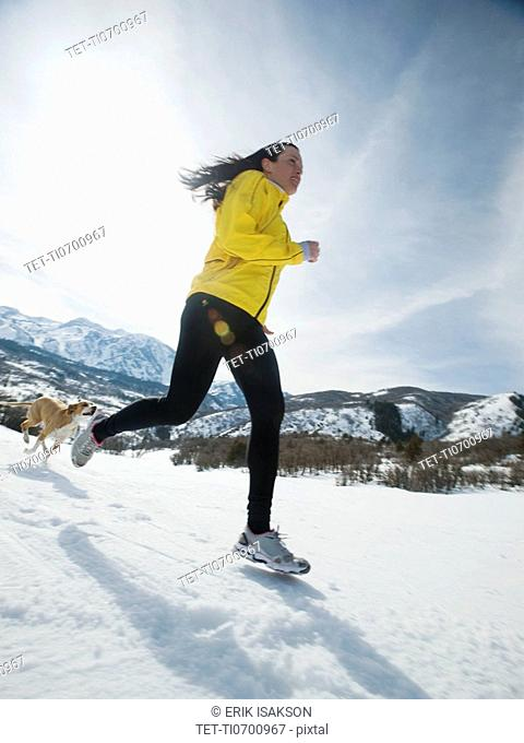 Woman and dog running in snow
