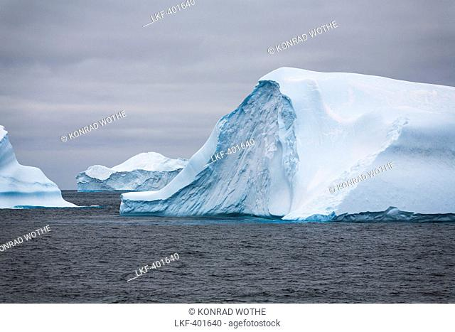 Blue icebergs with Laurie Island, Washington Strait, South Orkneys, Southern Ocean, Antarctica