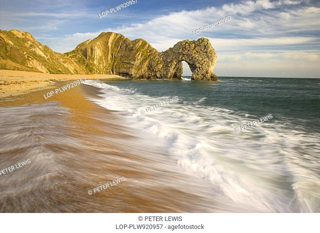 England, Dorset, Durdle Door, Waves rolling onto the beach by Durdle Door, a natural limestone arch on the Jurassic Coast in Dorset