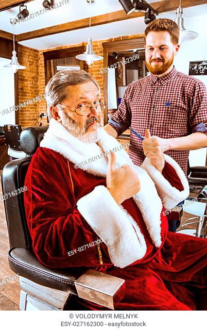 The senior man in Santa claus costume shaving his personal master at barber shop before Christmas