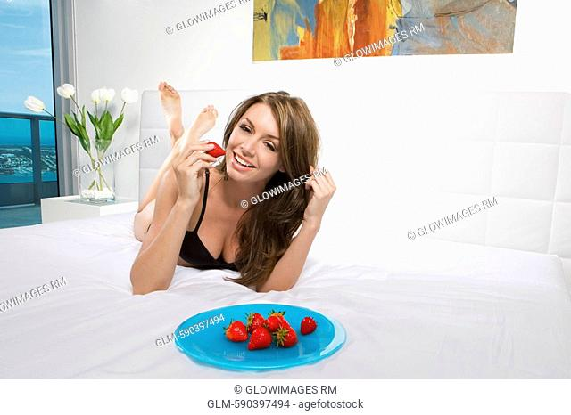 Young woman holding a strawberry and smiling