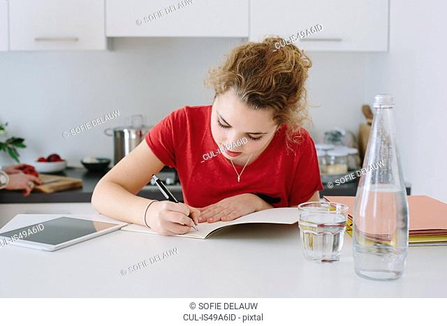 Teenage girl doing homework in kitchen