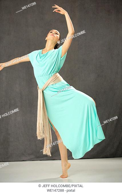 Beautiful young woman full length in green summer dress, dancing with tan scarf tied around her waist