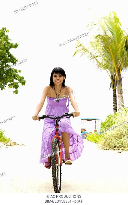 Chinese woman riding bicycle on tropical beach