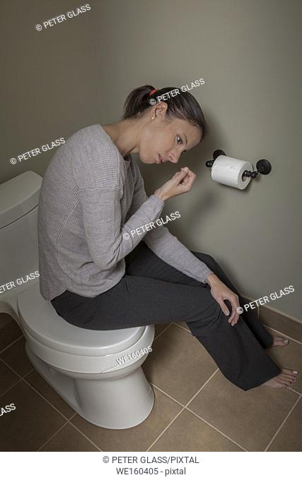 Young woman sitting on her closed toilet lid