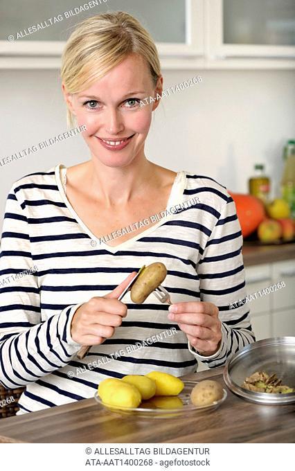 Woman is peeling potatoes