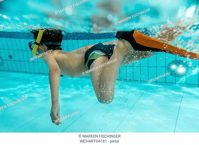 Boy with diving goggles, flippers and snorkel under water in swimming pool
