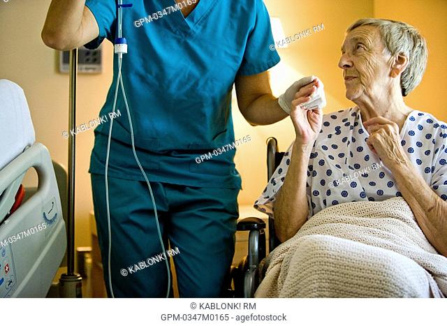 Senior woman in wheelchair next to nurse in hospital room