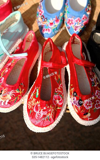 Traditional style hand made embroidered shoes for sale on old town street  Town of Guandu  Kunming  China