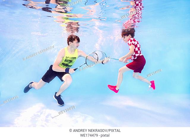 Two teenagers playing badminton underwater