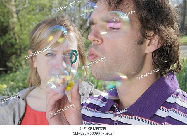 Couple blowing bubbles in park