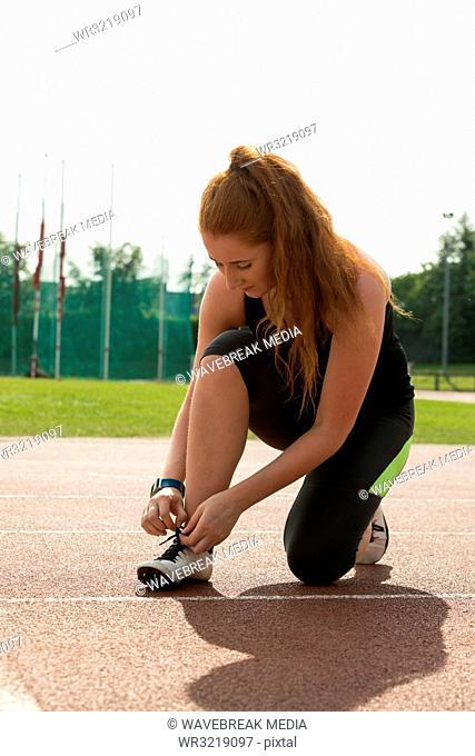 Female athletic tying shoe laces on running track
