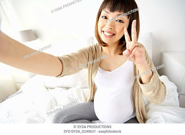 pregnant woman taking selfie in bed at home