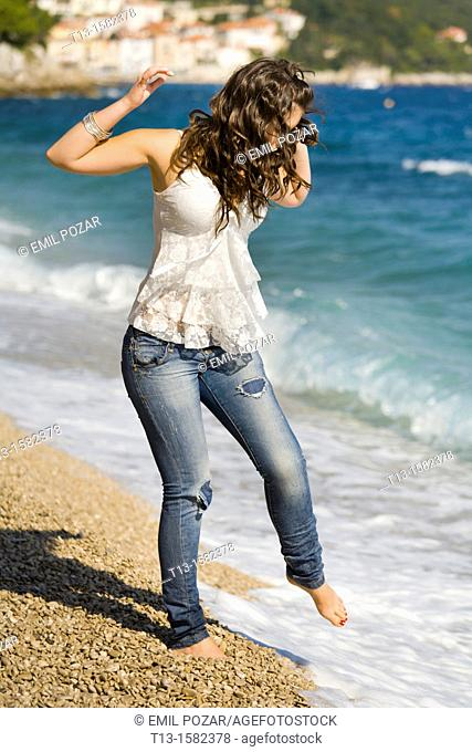 Attractive young woman is testing water with a bare foot