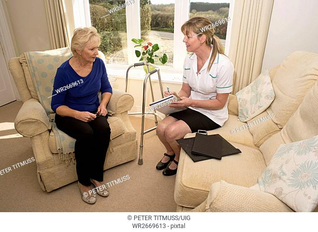 Nurse on a home visit talking with an elderly female patient