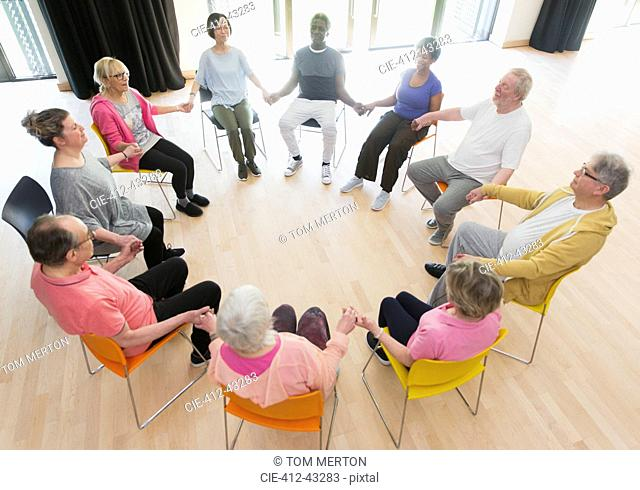 Active seniors holding hands in circle, meditating in community center