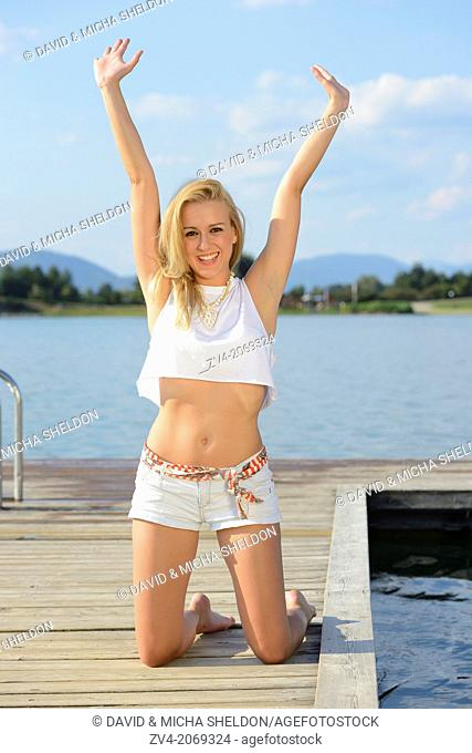 Young woman on a jetty at a lake in Austria