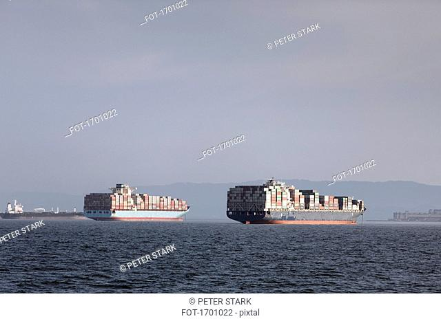 Mid distant view of container ships moored on sea against sky