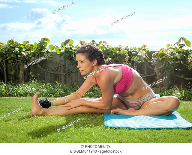 Mixed race amputee stretching in grass