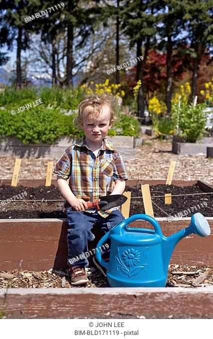 Caucasian boy holding spade with watering can in garden