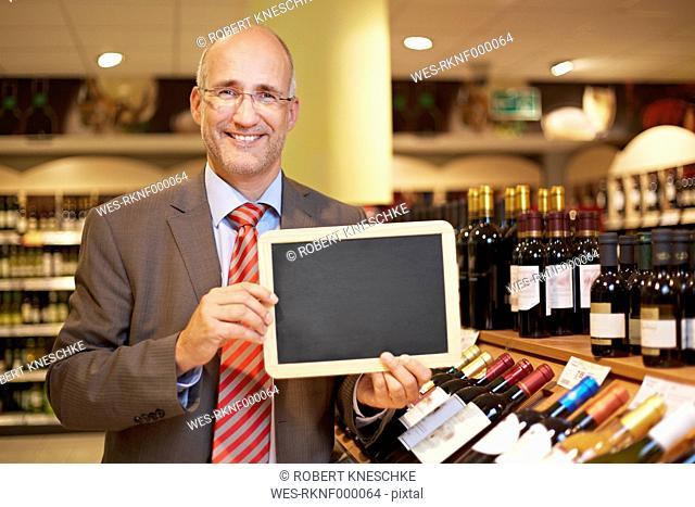 Germany, Cologne, Mature man holding blackboard in supermarket, smiling