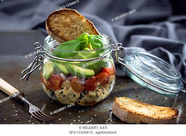Marinated tofu with sesame seeds, tomatoes, shallots, avocado and toast in a glass jar
