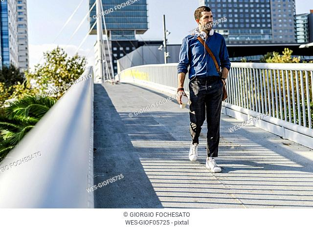 Man with headphones and coffee to go walking on a footbridge