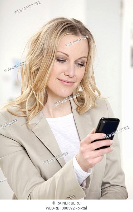 Germany, Bavaria, Munich, Businesswoman with cell phone in office, smiling