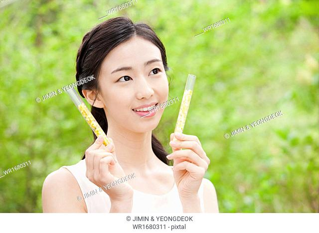 a woman holding two cosmetic items in the nature
