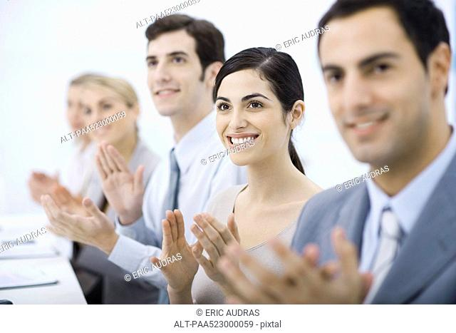 Group of professionals clapping, smiling, focus on one woman