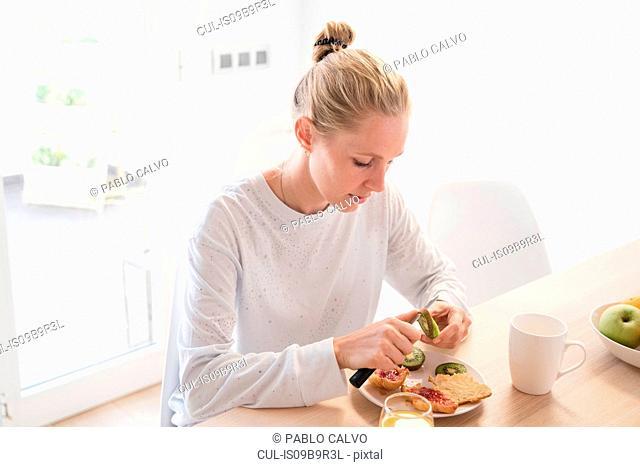 Young woman peeling kiwi fruit at breakfast table