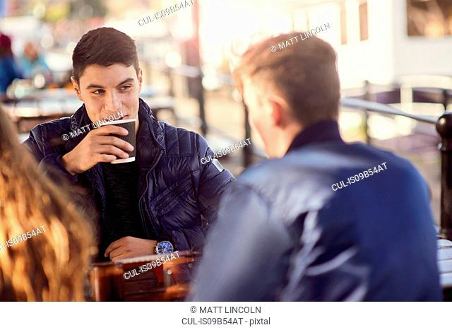 Three friends sitting outdoors, drinking coffee, Bristol, UK
