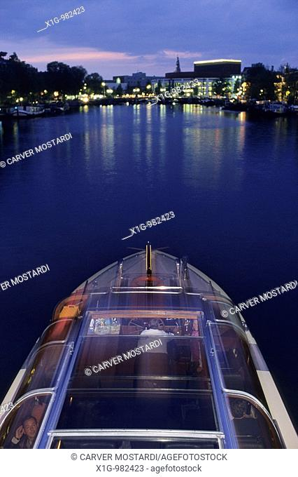 A canal boat cruising west along the Amstel river at night in Amsterdam, Netherlands