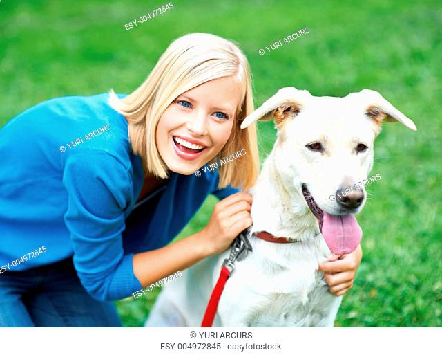 Smiling young woman outdoors with her cute labrador