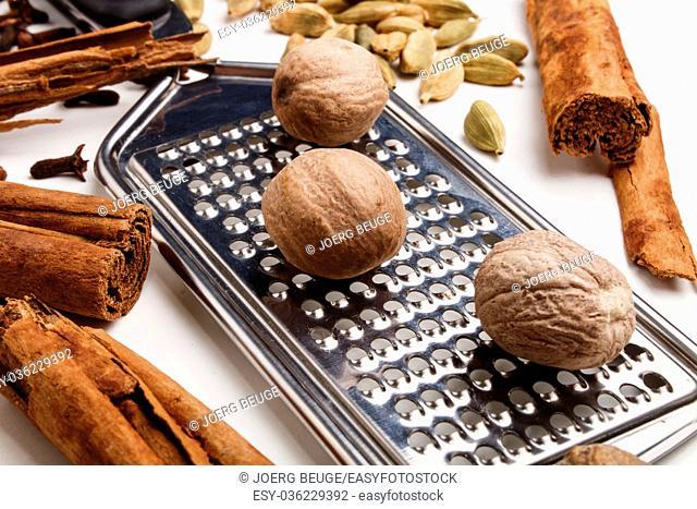 christmas spices, nutmeg, cinnamon sticks, cloves and cardamom on a bright background