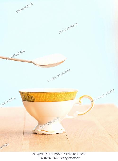 Spoon filled with sugar and cup. Conceptual image of using too much sweetener and unhealthy eating and drinking