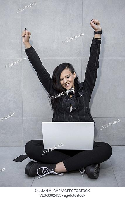 Cheerful woman sitting at laptop and celebrating with hands up