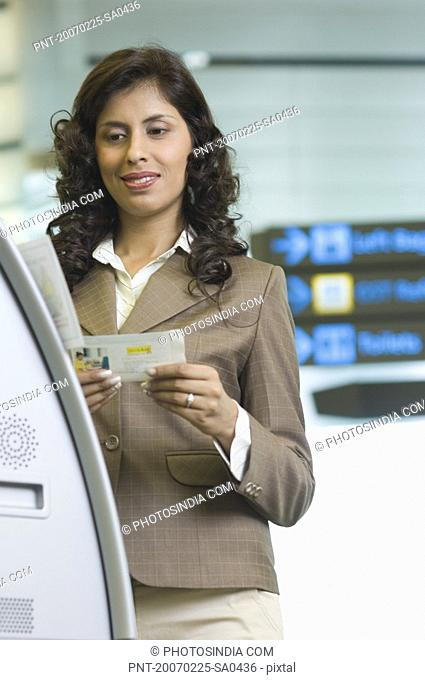 Close-up of a businesswoman standing in front of an automatic ticket machine and holding her boarding pass