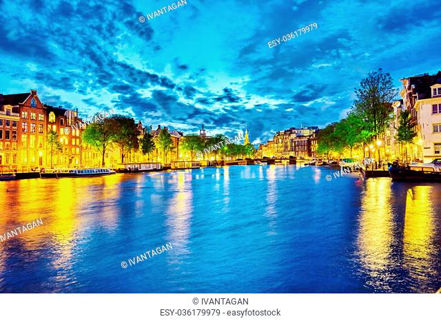 Famous Amstel river and night view of beautiful Amsterdam city