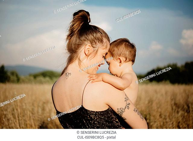 Woman with baby girl on golden grass field, Arezzo, Tuscany, Italy