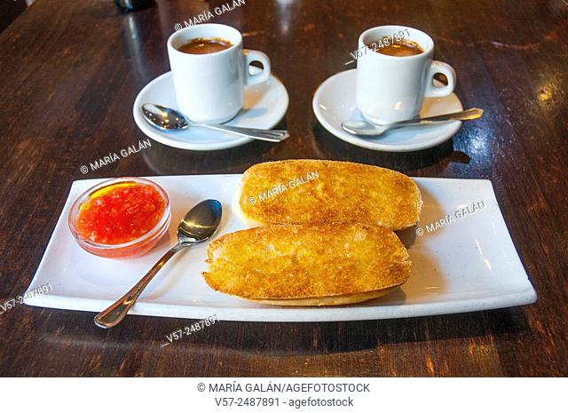 Spanish breakfast: two cups of coffee and bread with olive oil and tomato